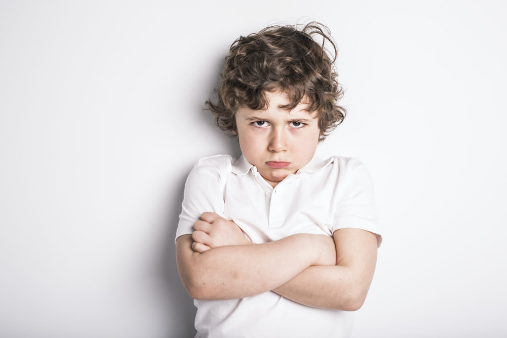 A Head and Shoulders Close Up Portrait of Young boy with Sulk attitude