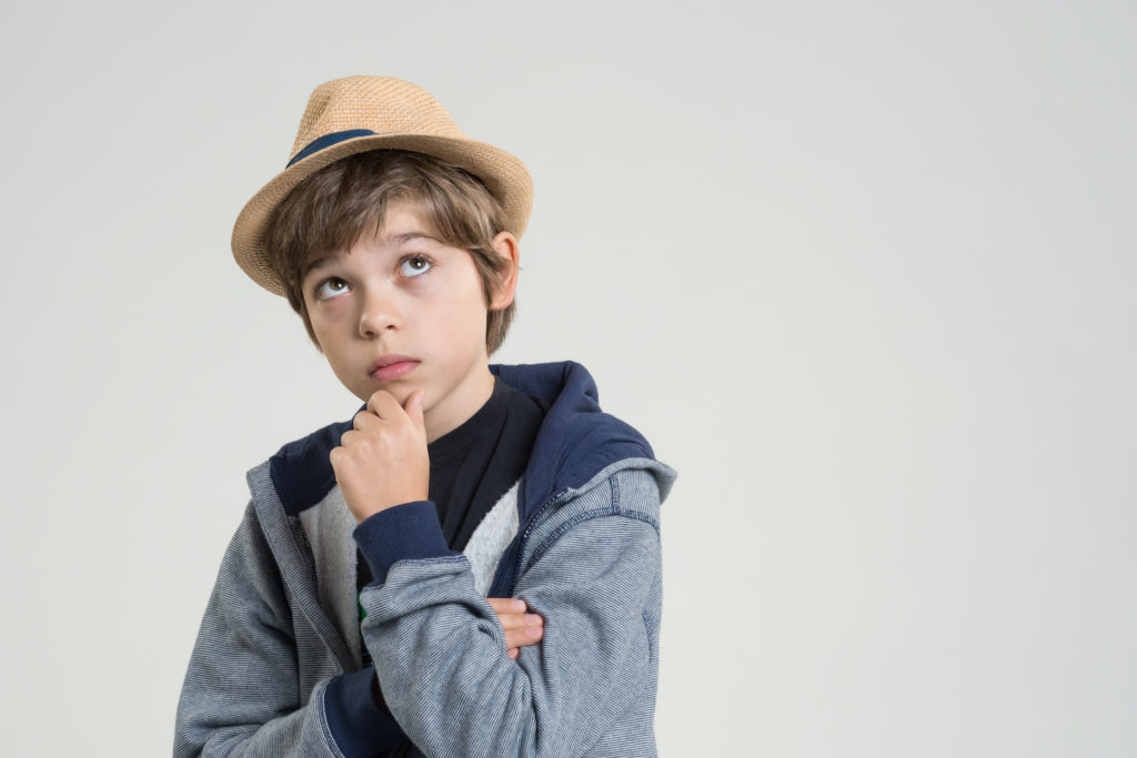 Young boy thinking. He puts his hand iat his jaw and looks up. Isolated on light gray background. Studio shot.    (Young boy thinking. He puts his hand iat his jaw and looks up. Isolated on light gray background. Studio shot.   , ASCII, 114 components