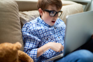 Shocked boy in eyeglasses sitting on sofa and using laptop, he playing video game