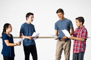 A group of diverse students reading lines for drama