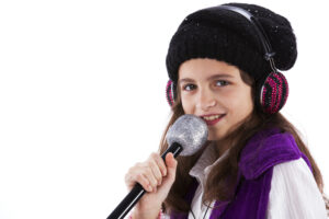 Female child singing with a mic and headphones