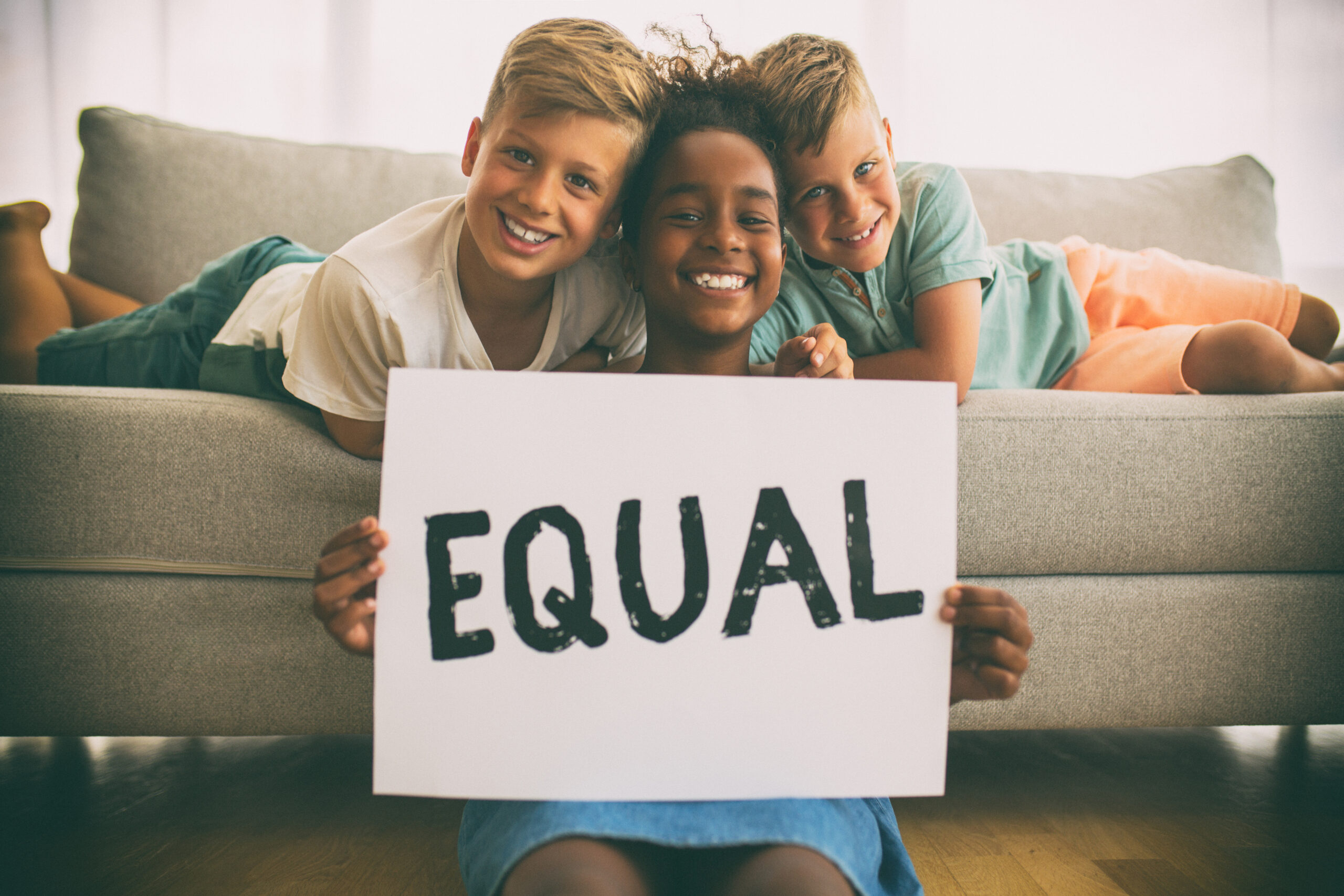 African american girl sitting on the floor  and her friends lying on the sofa behind her. They are smiling and looking at the camera. Girl is showing an message that says Equal.