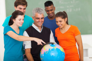 group of happy high school students and teacher looking at globe