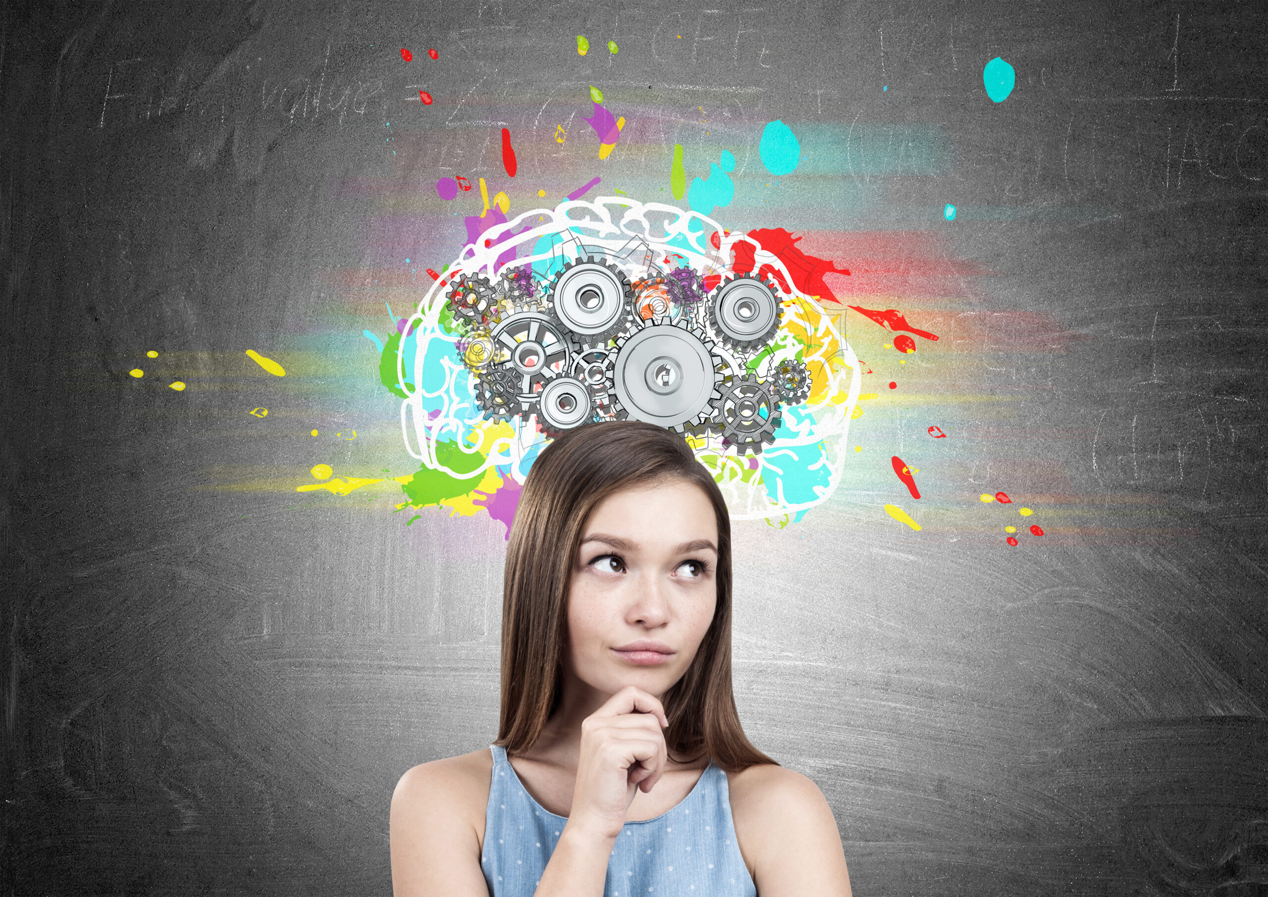 Portrait of a dreamy teen girl wearing a blue dress and holding her hands near the face. She is standing near a blackboard with a colorful brain sketch and gears on top of it
